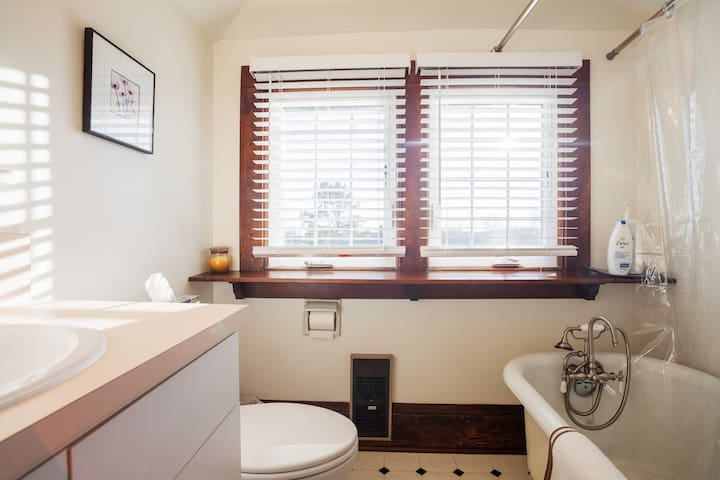 Fully equipped bathroom with vintage clawfoot soaker tub.