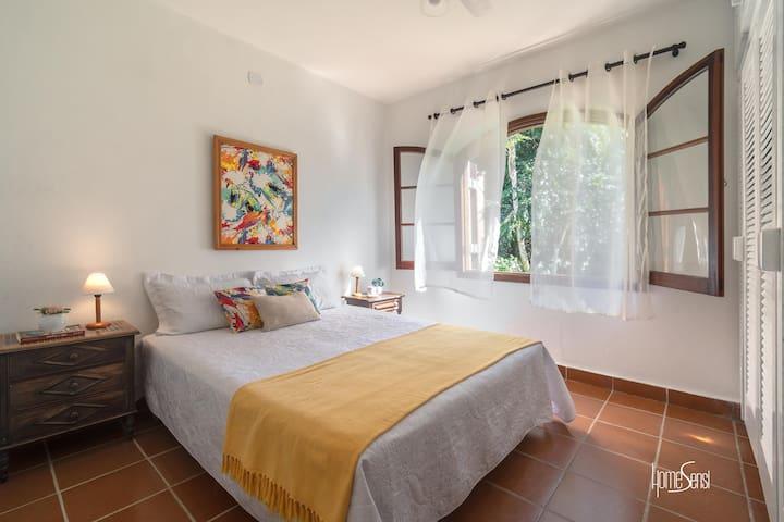 Quarto com cama de casal e vista para o terreno da casa
