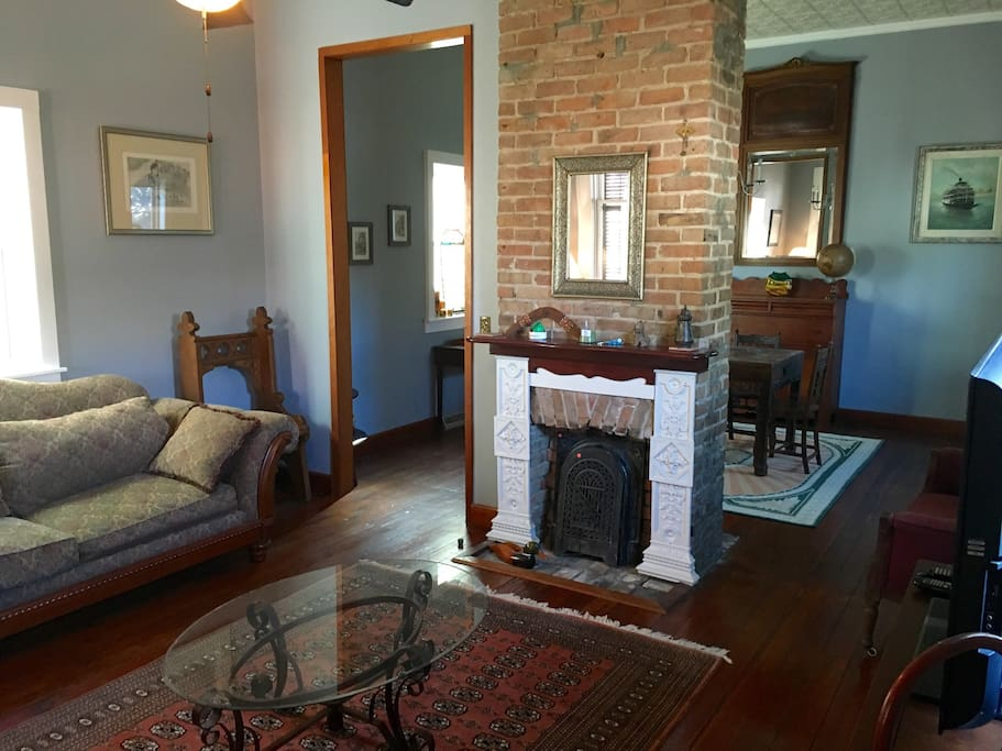 The exposed brick fireplace divides the living room and the dining room.