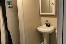 Bathroom has a stand up shower with shampoo, conditioner and soap dispenser.