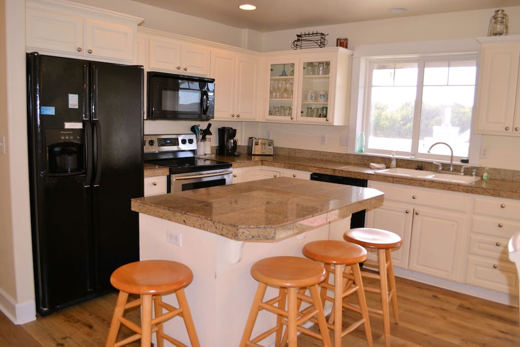 Upper level fully equipped kitchen with granite counter tops, prep island/breakfast bar for 3, dining table for 8 and a slider out to deck