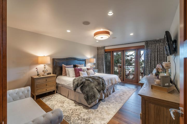 """The master bedroom includes a king bed, ceiling fan, comfy bench, 68"""" TV and a sound system as well double doors onto a private patio."""