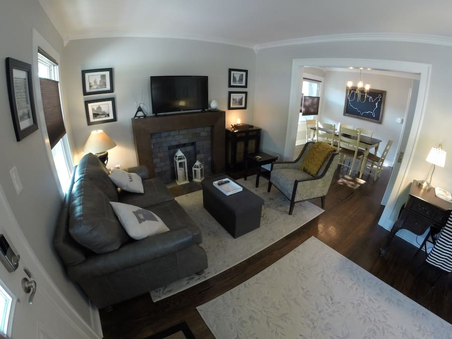 Living room with seating area, faux fireplace, new 42-inch smart TV, new leather loveseat, chair, and trunk, plus vintage Kansas City art photographs