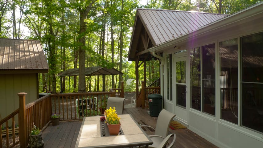 Back deck and carport in background, sunroom to the right and carport in