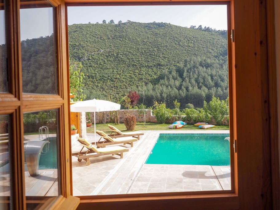 The bedroom door / window offers relaxing views of the pool and lush green hills.