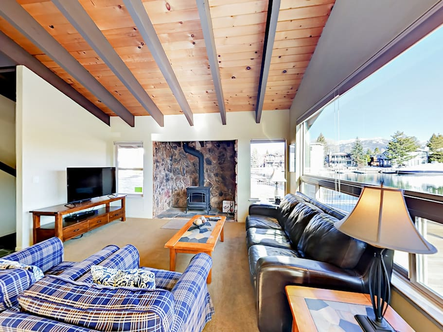 The grand living space boasts vaulted beam ceilings, impressive windows, and a wood burning fireplace.