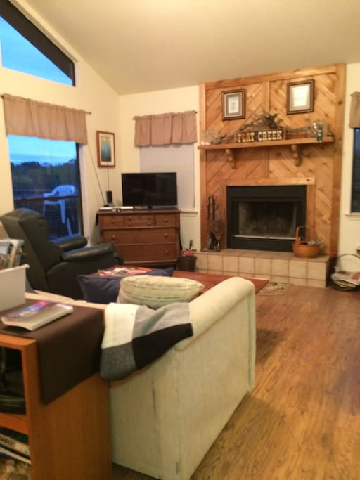 The living room has a lovely wood burning fireplace and huge windows.