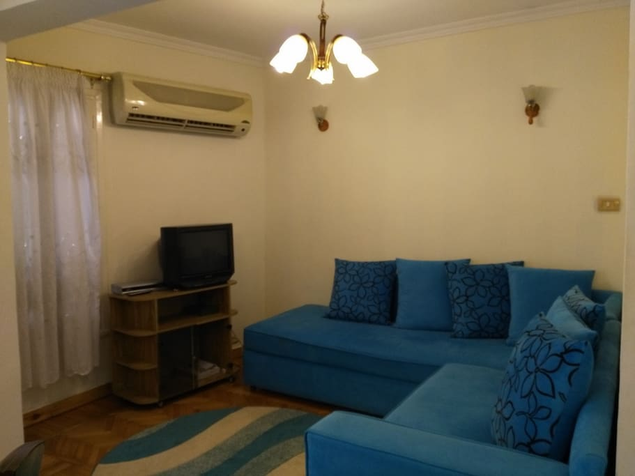 Living room: Couch, TV, satellite channels and an air conditioner