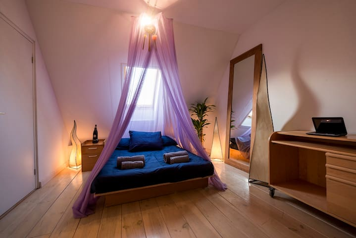 Spacious bedroom with private entrance, double bed, closet, couch and space for a desk.