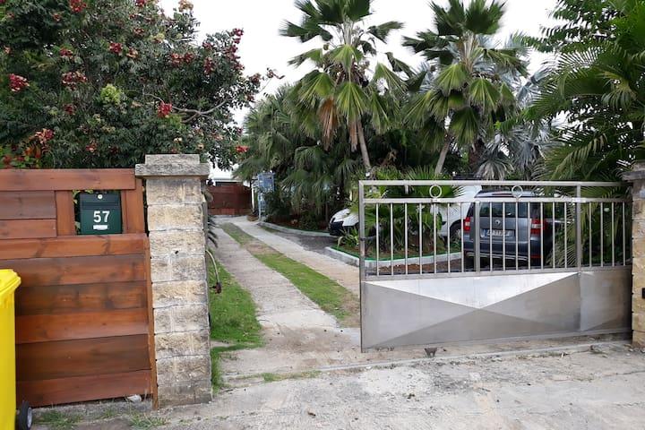 Entrée de la propriété et parking réservé au logement avec portail automatique