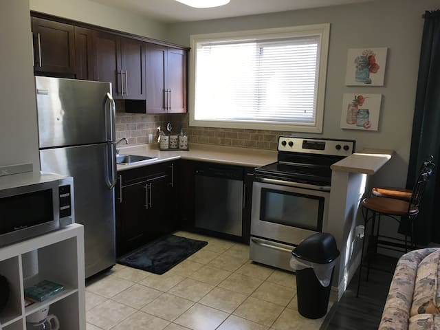 Fully equipped kitchen includes dishwasher, microwave, eating bar, dishes, pots and pans, etc.
