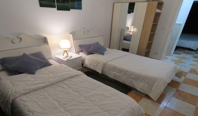 3ème chambre à deux lits de 90cm sur 2m chacun, armoire, un téléviseur à écran plat accroché au mur.