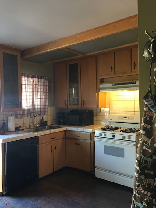 Fully stocked kitchen with fridge, appliances, coffee maker and utensils and dishes and cookware