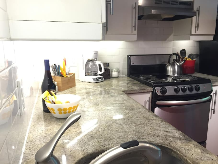 Kitchen with granite counters, dishwasher, microwave, and stocked with essentials like coffee