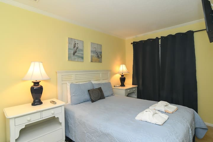 Full bed in the private bedroom with blackout drapes.