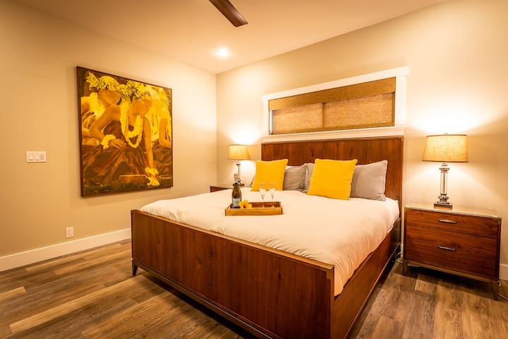 Master Bedroom: luxurious king size bed with a large hula-scene painting. Also opens with sliding glass doors to the lanai (veranda)