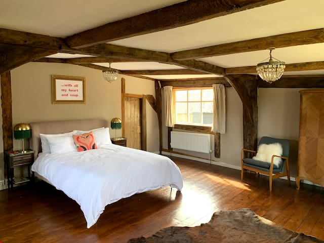 The master bedroom has beautiful beams and a kingsized bed with pure french linen bedding
