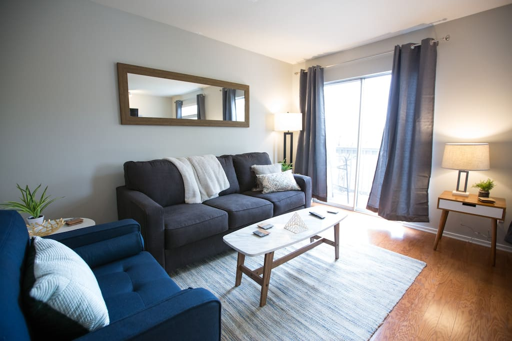 """You'll feel comfy, cozy, and refreshed in our stylish living room. A great place to crash after being out on the town! Enjoy our 55"""" Smart TV. You can also relax on the balcony that overlooks the river! You can also relax on the balcony that overlooks the river!"""