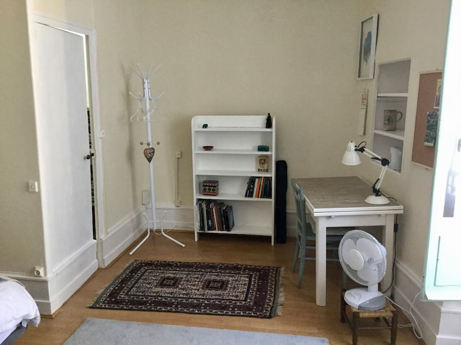 Bookshelves and work table with lamp, noticeboard and electric fan