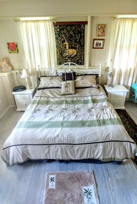 Comfortable King size bed under ceiling fan.