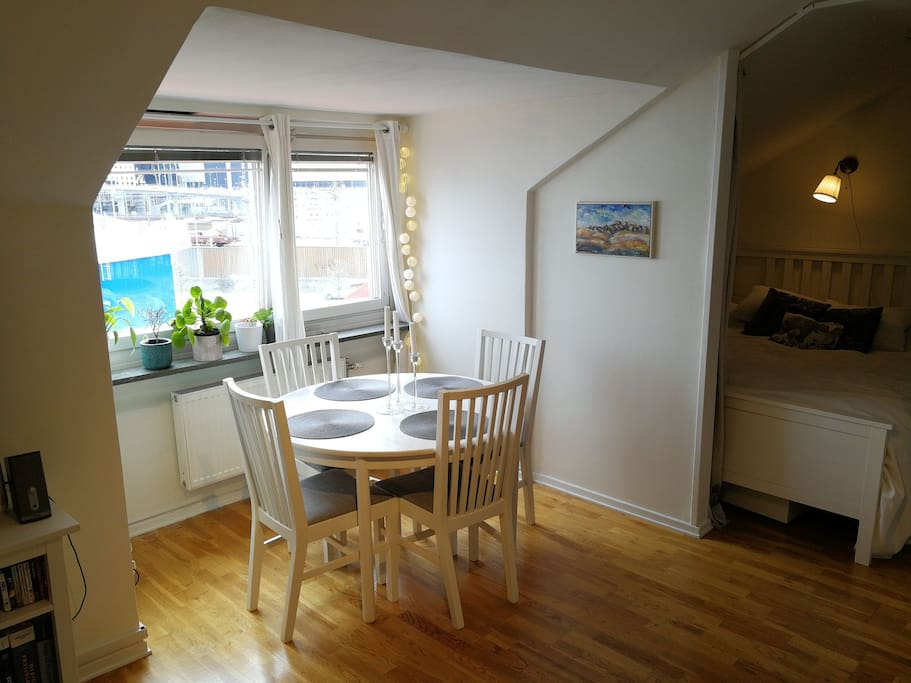 A dining table with space for 4 people stands next to the south-facing window in the living room.