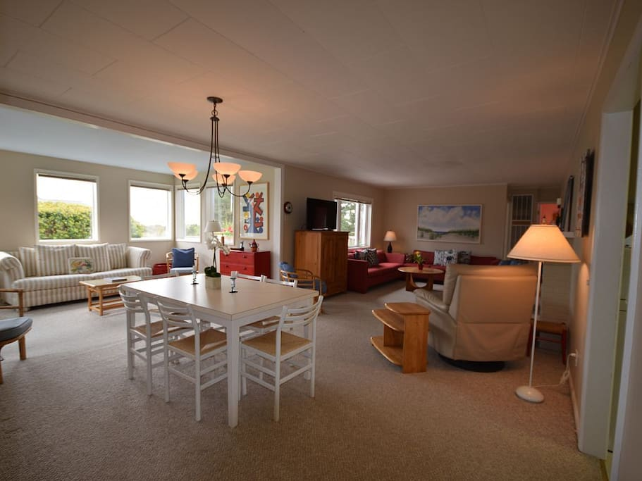 Large open concept living and dining area with peekaboo views of the ocean.