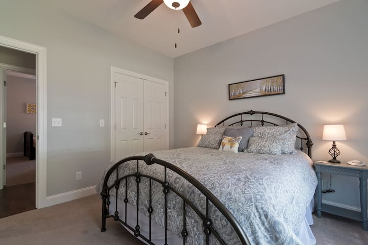 This cozy queen bed is fitted with clean sheets, a warm comforter, and lots of pillows.