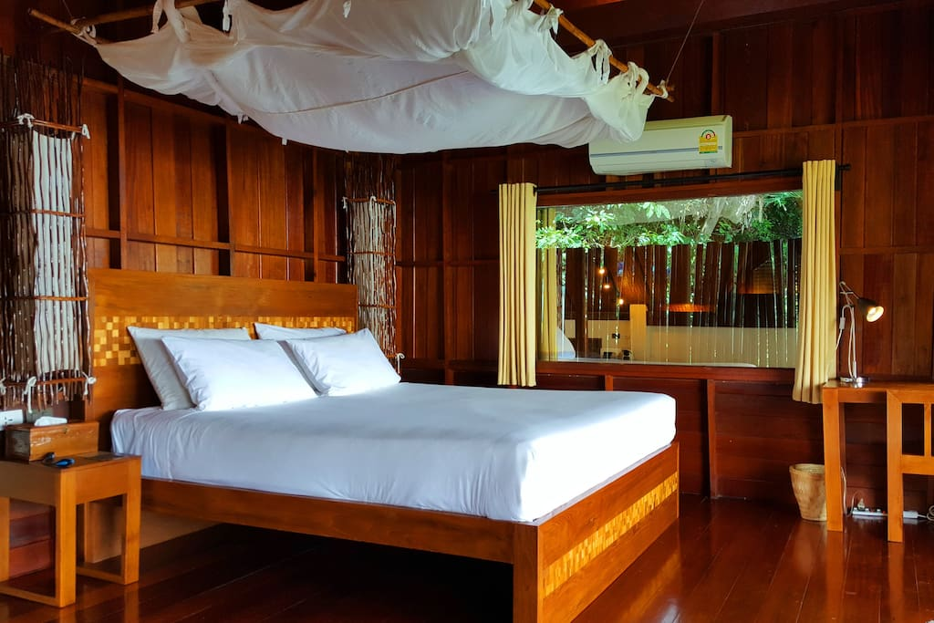 King-sized bed with mosquito net and sea view