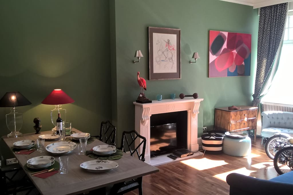 A bright british green Sitting and dining room. The TV is hidden in the fire place.