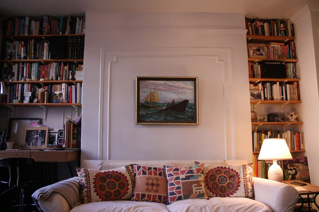 Living room: comfy couch, desk, and bookshelves