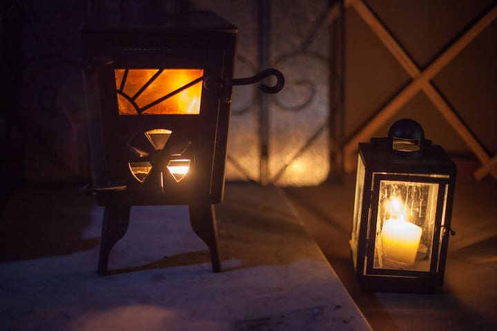 The woodburing stove and a candle lamp cast a warm light