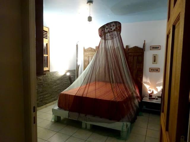 la Chambre avec son lit double avec moustiquaire