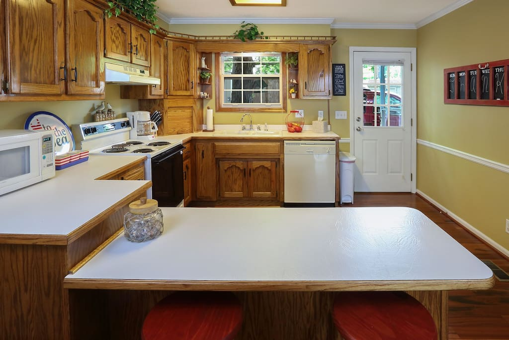 Fully furnished kitchen with oven, dishwasher, garbage disposal, and coffee pot.
