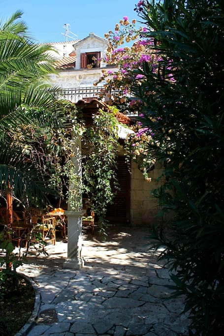 The  large and furnished garden packed with plants and flowers surrounds the villa.