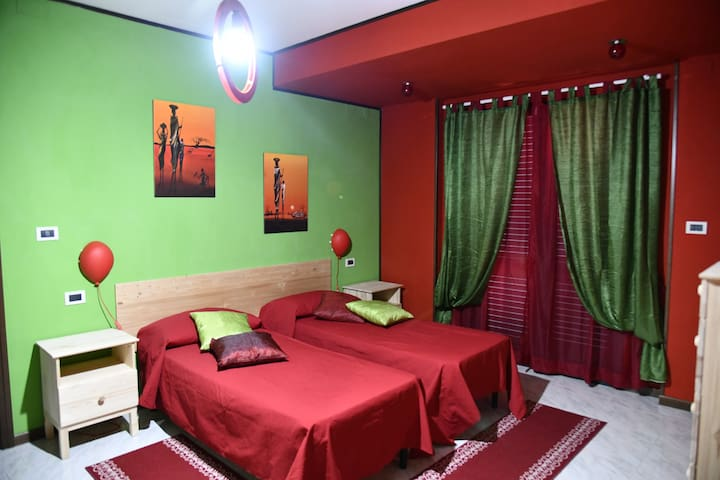 """Camera """"rossa"""": due letti singoli,  tv e uscita su ampio terrazzo (primo piano)"""