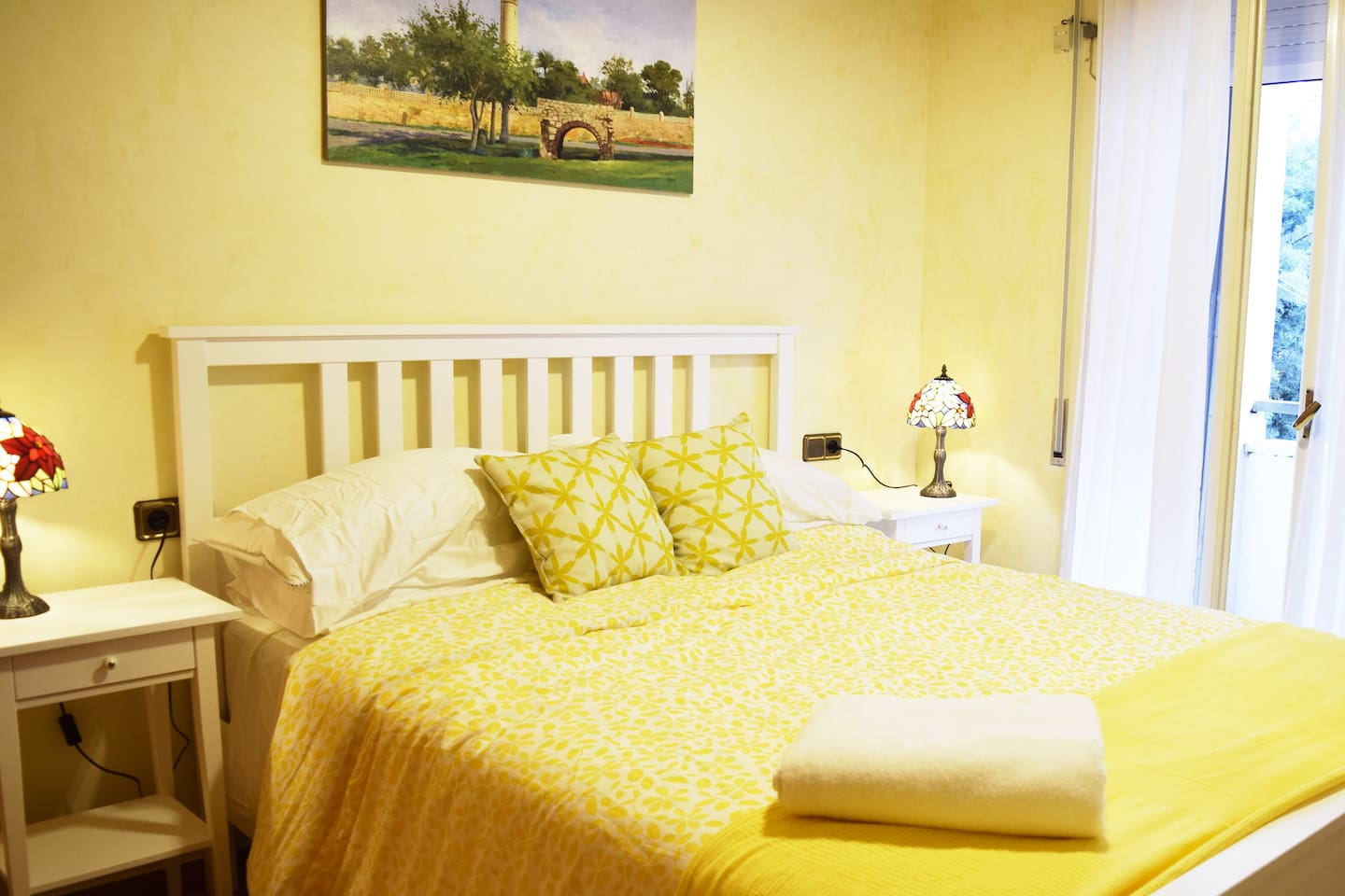 West Queen Room with original painting of the Vilanova lighthouse. Nightstand and tiffany lamp on each side of the bed.  West-facing window opens onto balcony overlooking the quiet private garden. Security blind can be closed for complete black-out.