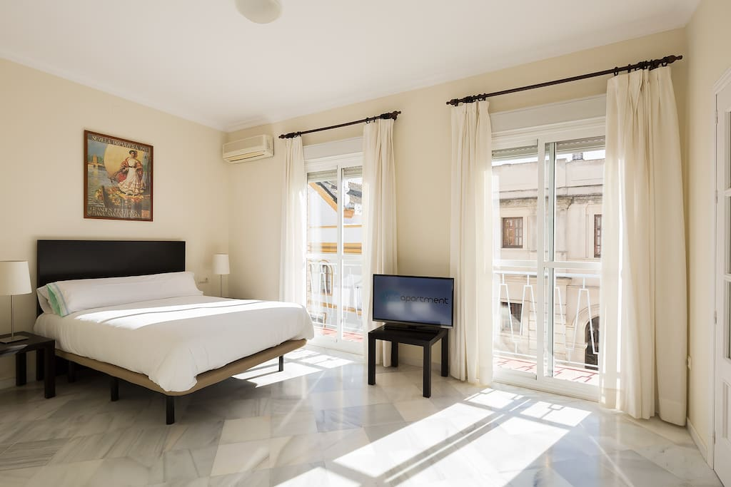 Master bedroom with a double bed. Two windows face the pedestrian Rioja street.