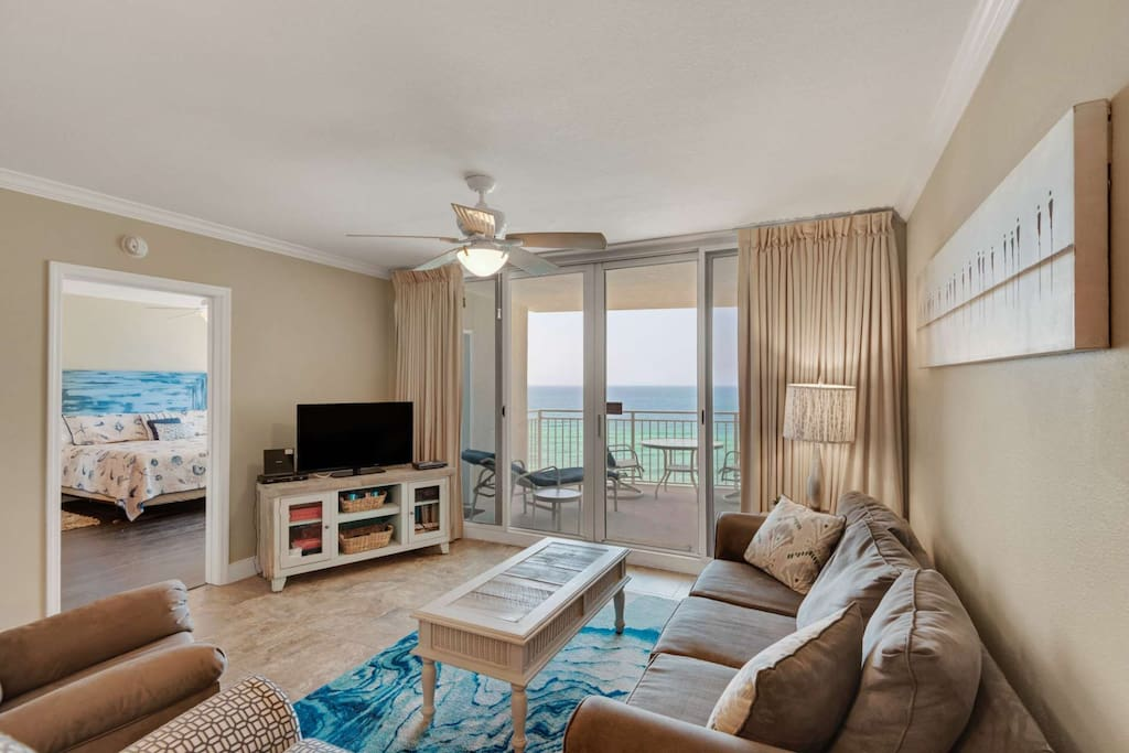 Beachy decor with balcony access and queen sleeper sofa in the living area.