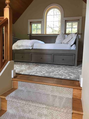 Stairs to landing and a full sized day bed with twin trundle