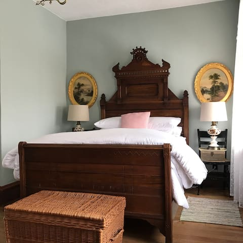 The north bedroom on the second floor has a matching sunflower motif double bed and dresser. Various antique landscapes are highlighted on the blue green walls.