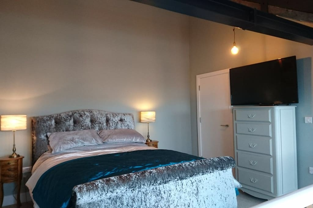 Master bedroom with super king size bed, wardrobe, and en suite