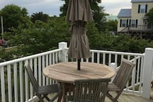 Dining table with large umbrella on upper side deck.  Great place for an evening dinner or to view July 4th fireworks!