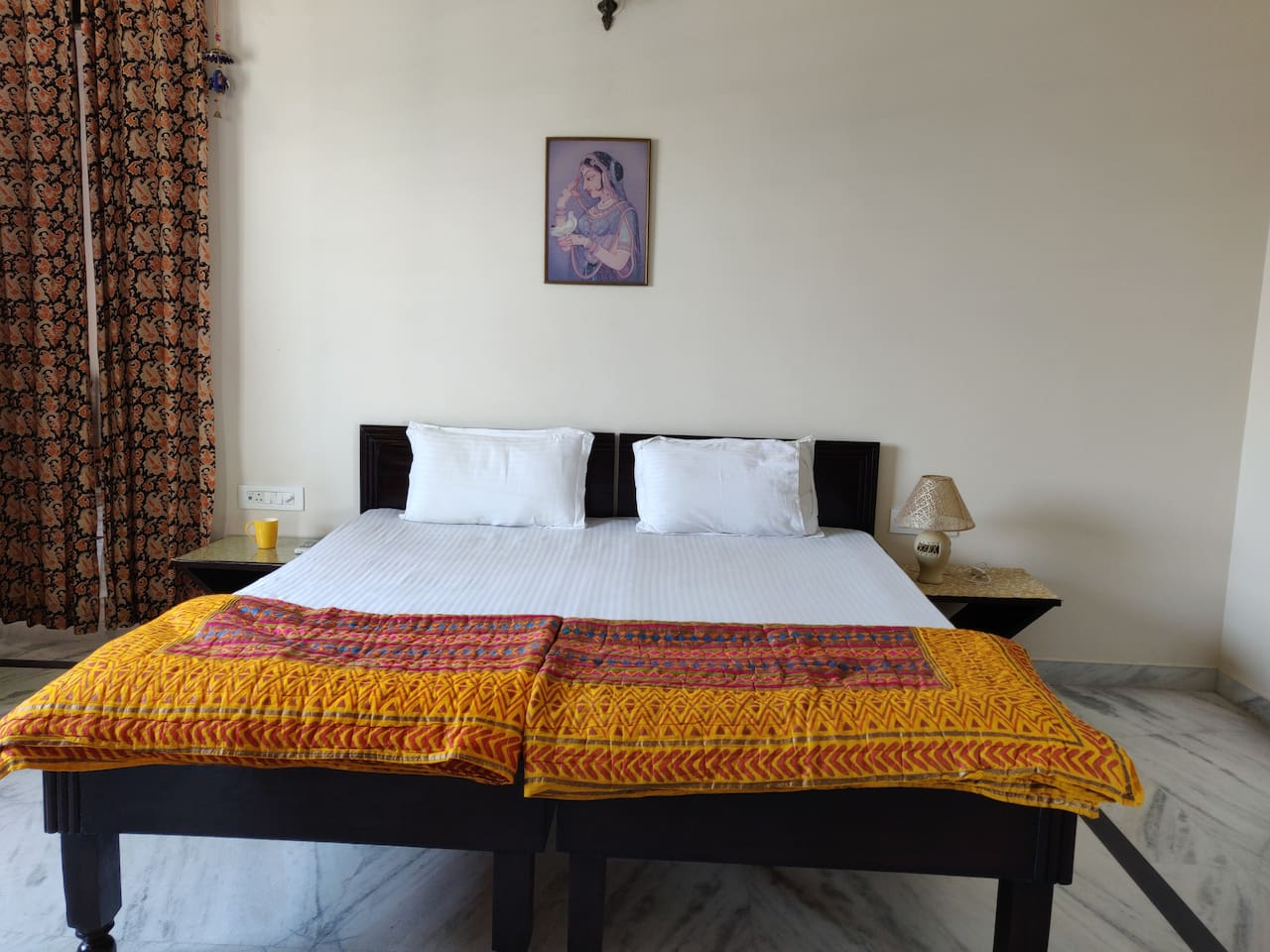 Spacious, clean and tidy bedroom with ethnic linen.