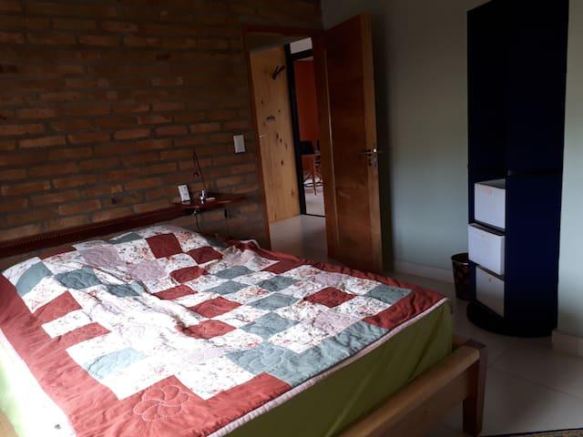 Pieza con cama matrimonial, aire y espacio para colocar su ropa.  Guest room with a king-size bed and air-conditioner.  Gästezimmer mit Schrankplatz und airconditioner.