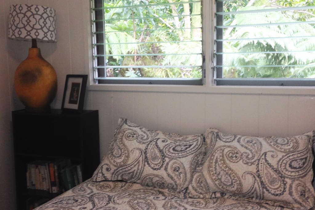 Guest bedroom with queen bed with light quilt. Hawaiian jungle right outside your window.