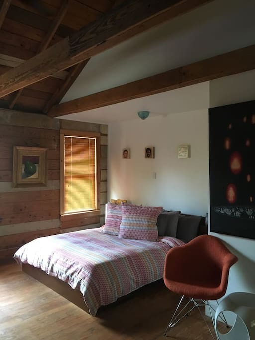 Main sleeping area surrounded in original exposed heart of pine shiplap from 1920 and vaulted beamed ceiling