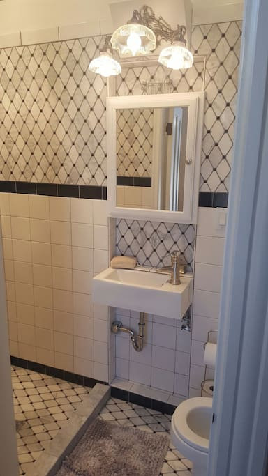 Enjoy a hot shower in this Art Deco argyle-tiled bathroom next to your room.