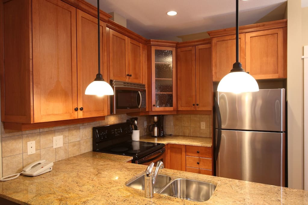 The gourmet kitchen features granite countertops and stainless steel appliances