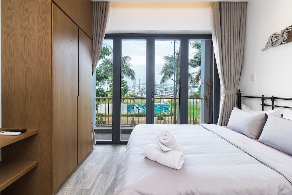 The bed next to a balcony full of natural light and green view great for relaxing your body and mind.