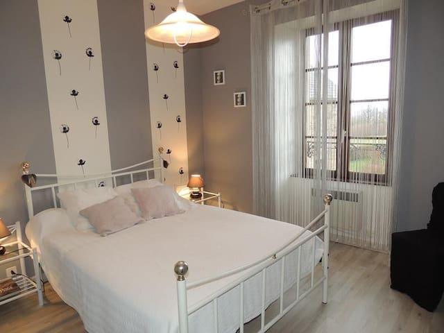 Chambre avec un lit double , deux chevets et une commode.